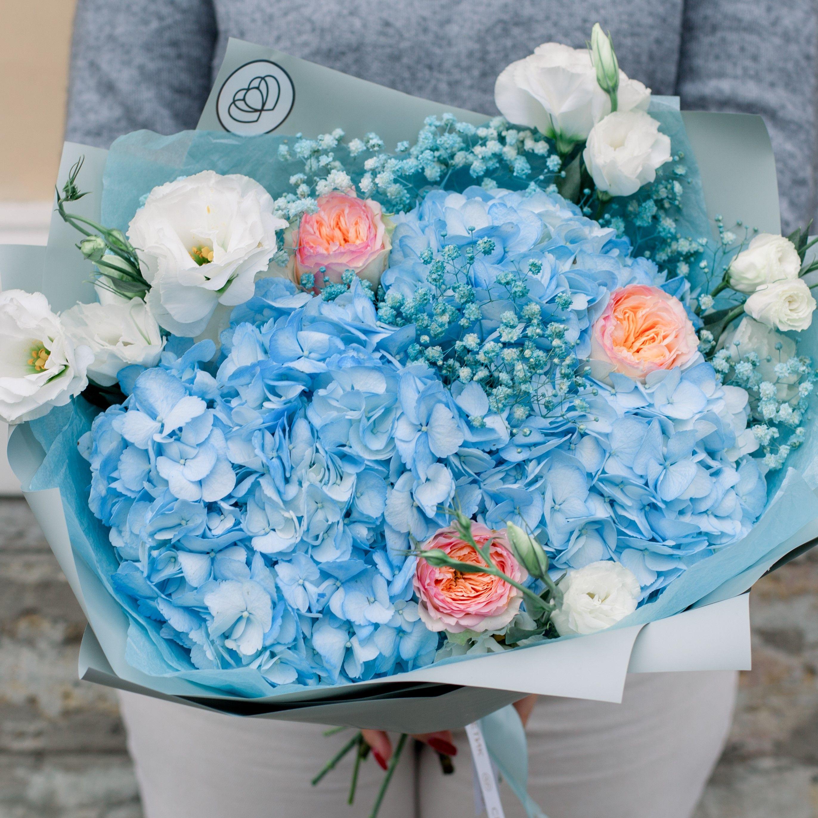 Букет из 3 голубых гортензий, 3 роз пионовидных, 5 белых лизиантусов и голубой гипсофилы в упаковке фото