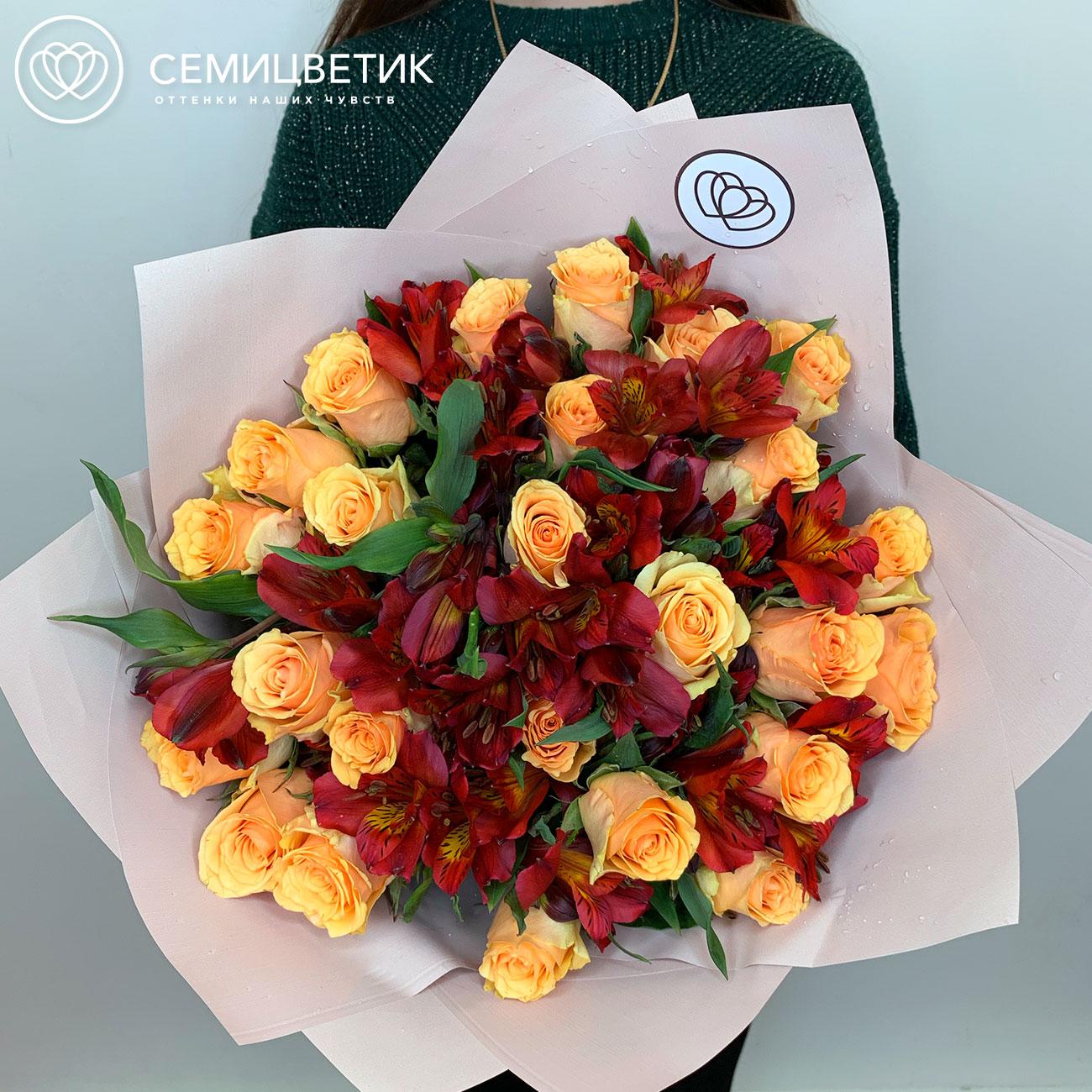 Красно-желтый букет из 25 роз и 10 альстромерий в дизайнерской пленке фото